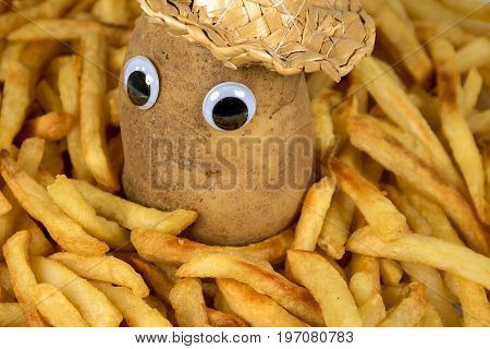 raw potato with straw hat and eyeballs in a pile of golden french fries