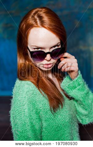young redhead girl in greem pullover and sunglasses over dark blue background. beauty model woman with luxurious red hair. hairstyle. holiday makeup