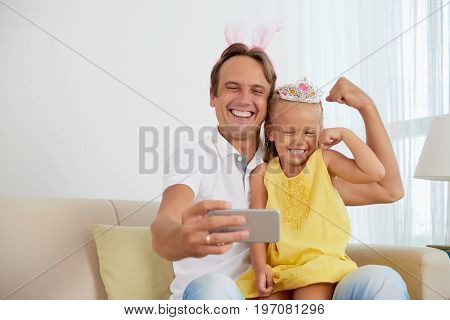Happy father and daughter showing their biceps when taking selfie