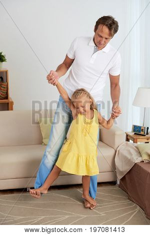 Daughter standing on fathers feet when they are playing at home