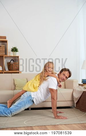 Man doing push-ups with daughter lying on his back