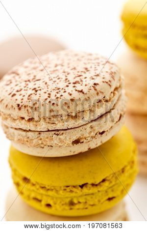 closeup of some stacks of appetizing macarons with different colors and flavors on a white background