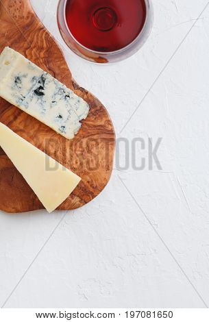 The glass of red wine, blue cheese and parmesan on the beautiful wooden plank of olive wood on the textured white background.