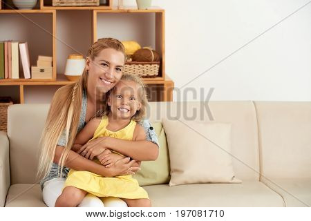 Portrait of happy mother hugging her little daughter and looking at camera