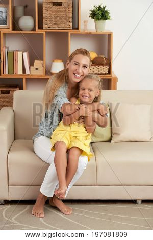 Happy mother and daughter playing together at home