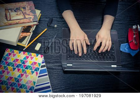 Girl student is Studying on a wooden desk by using a computer . There are books pens rubber USB stick and notebooks around her.
