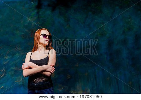 beautiful girl with red hair in black shirt and sunglasses over dark blue background. beauty model woman with luxurious red hair. hairstyle. holiday makeup