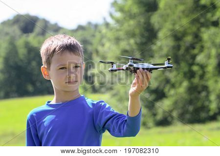 Child playing with drone outdoors at summer day
