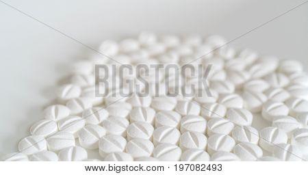 Pile of white pills on white background