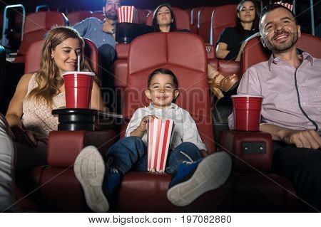 Portrait of a cute Hispanic boy sitting in the movie theater with his parents and looking happy