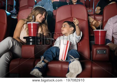 Kid sitting in the cinema theater with his parents and getting excited about the movie