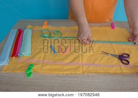 Tailor cutting fabric using large scissors or shears as he follows the chalk markings of the pattern close up of his hands. Woman's Hand Sewing Quilt
