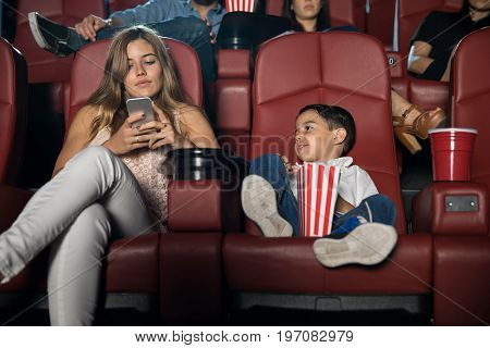 Portrait of a pretty young woman using her smartphone and getting distracted while sitting in a movie theater with her son