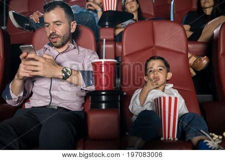 Busy dad looking at his phone while sitting in a movie theater with his son
