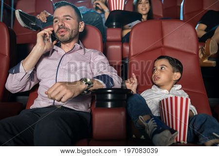 Little boy looking disappointed with his dad and asking him to be quiet while he talks on the phone at the movie theater
