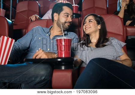Happy Hispanic couple enjoying their date at the movie theater and looking in love