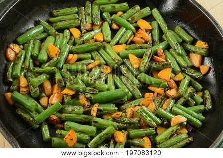 Blackened stir fry green beans and carrots in cast iron frying pan skillet