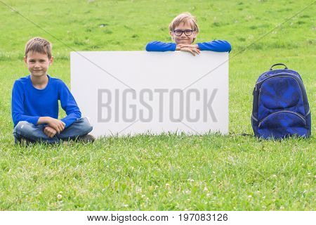 Children sitting on the grass against blank white placard board