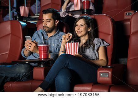 Boyfriend checking his phone while sitting at the movie theater on a date
