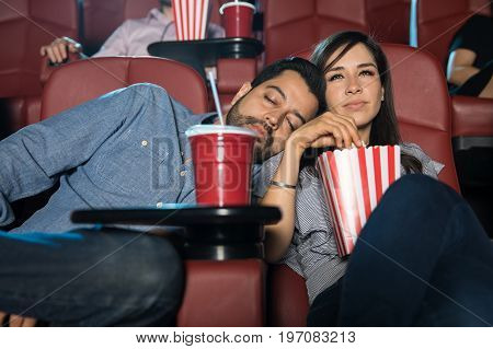 Bored man sleeping next to his girlfriend on a date while watching a chick flick at the movie theater