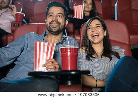 Latin couple laughing and having a good time while watching a comedy in the movie theater