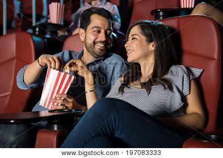 Happy Hispanic couple watching a movie at the cinema theater and sharing some popcorn