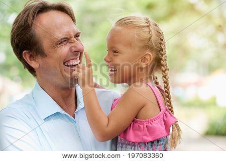 Cute little girl touching nose of her laughing father