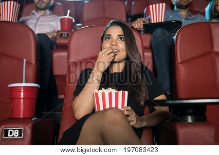 Pretty young brunette enjoying a movie and some popcorn by herself at the cinema theater