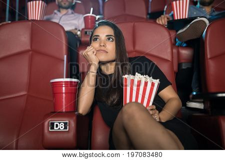 Attractive young brunette looking really bored at the movie theater