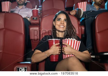 Pretty young smiling Hispanic woman hugging her snack combo of soda and popcorn at the movie theater
