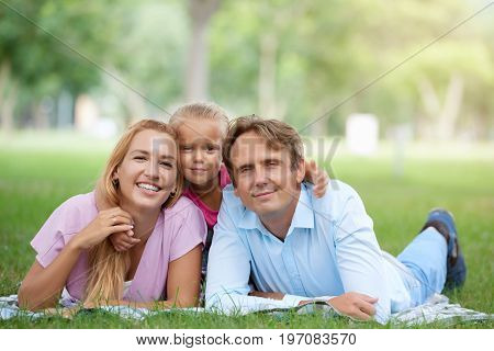 Happy family of three lying on blanket in the park