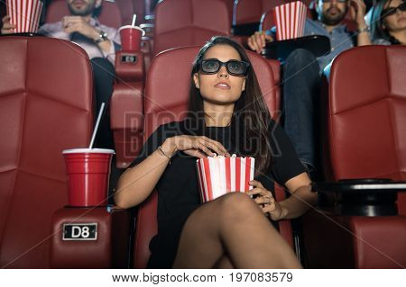 Portrait of a beautiful young woman watching a 3d film at the movie theater and eating some popcorn
