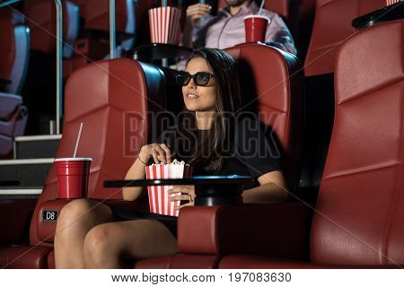 Good looking young brunette sitting by herself at the movie theater and watching a 3d film with some popcorn
