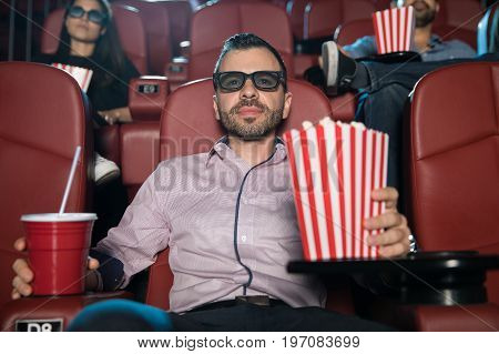 Good looking young man with 3d glasses watching a movie and eating popcorn at the theater