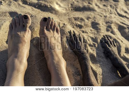 Photo of legs of young Caucasian girl and paw of dog in sand on summer beach. Selfi feet.