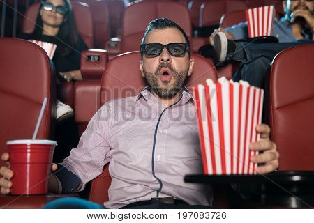 Hispanic man with 3d glasses looking surprised and excited by a scene at the movie theater
