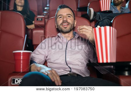Portrait of a handsome young Hispanic man sitting in a movie theater and eating some popcorn