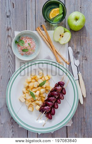 Grilled chicken hearts on skewers with stewed apples on a white plate