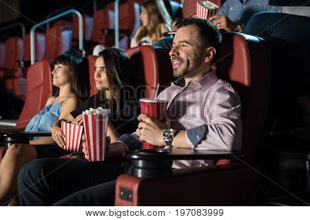 Crowd of good looking people eating snacks and having a good time at the movie theater