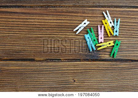 Wooden background with colored clothespins. Place for text. Top view.