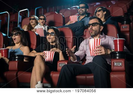 Small crowd of people looking really surprised while watching a 3d film at the movie theater
