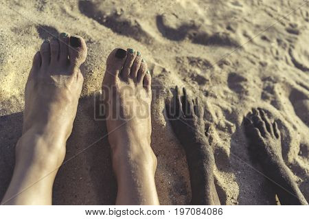 Photo of legs of young girl and paw of dog in sand on summer beach on the walk. selfie feet.