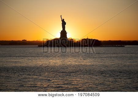 Sunset behind The statue of Liberty. USA