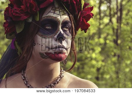 Beautiful woman in makeup traditional Mexican Calavera skull Katrina in the autumn forest in a wreath of red flowers. Day of the dead. Halloween celebration.