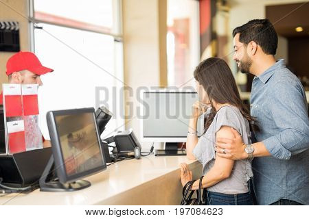 Couple Choosing A Movie At The Theater