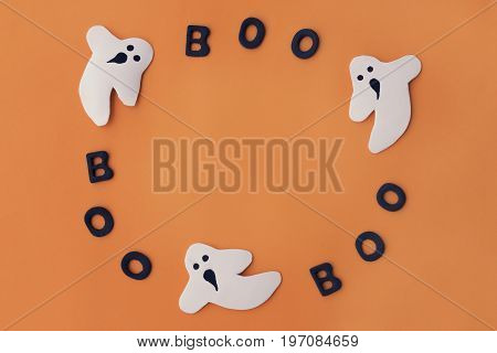 Handmade ghost and letters boo in a circle on orange paper background. Halloween holiday concept top view. Space for text.