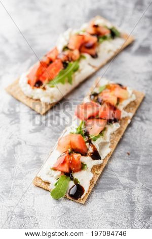 Healthy snack from crispbread crackers with mascarpone cheese arugula tomatoes and balsamic sauce