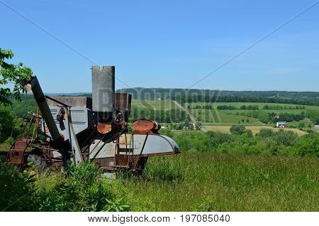 Antique Harvester Combine with backdrop of the farms and hills of upstate New York