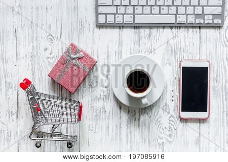 Online shopping concept. Shopping trolley near bank card and keyboard