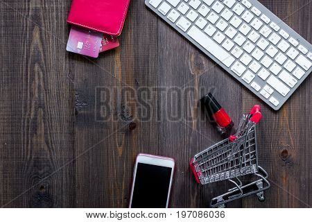 Online shopping concept. Shopping trolley near bank card and keyboard.